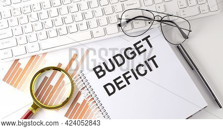 Budget Deficit Text Written On Notebook With Keyboard, Chart,and Glasses