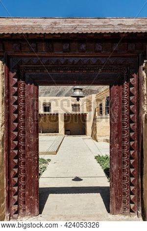 Gates with bell of Tabo monastery of Tibetan Buddhist Gelug sect. Monastery is built on high Himalaya plato in tradition of Tibetan Buddhism. Tabo village, Spiti valley, Himachal Pradesh, India