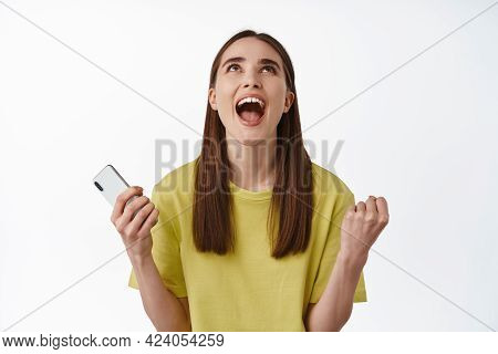 Thank God. Relieved And Happy Triumphing Girl Winning Prize, Money On Smartphone, Fist Pump, Looking
