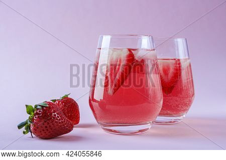 Two Glasses Of Cooling Strawberry Sangria With Sparkling Wine, Strawberry, Ice Cubes In Champagne Gl
