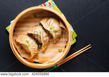 Food Concept Homemade Jiaozi Chinese Dumpling In Bamboo Streamer Basket On Black Background With Cop