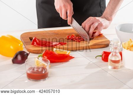 Man Cutting Red Pepper On A Wooden Board