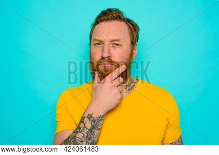 Man With Yellow T-shirt And Beard Is Very Undecided