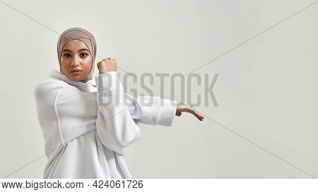 Cute Young Arabian Girl In Hijab And Hoodie Doing Warm Up While Looking At Camera On White Backgroun