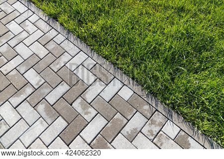 Cobbled Road And Green Grass. Concrete Street Pavement, Top View, Abstract Background Photo Texture