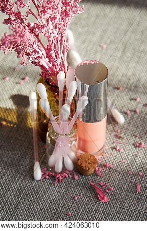 Sunlit Shiny Pink Lip Gloss Bottle With Other Cosmetics Tubes On The Makeup Desk. Fashion And Cosmet