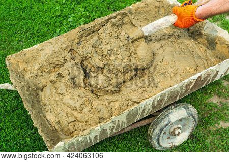 Master Builder Mixes The Building Mixture In Cart For Laying Stone. Close-up Of A Builder Is Hand Wi