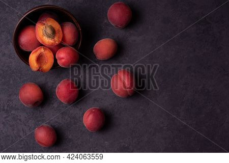 Fresh Apricots On A Dark Brown Background, Dark Mood, Copy Space, Close Up.