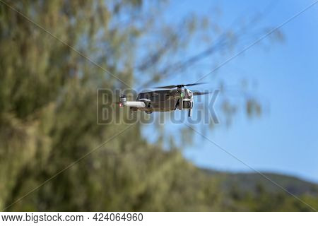 A Drone Hovering Over Coastal Trees Ready To Takeoff And Photograph The Picturesque Environment