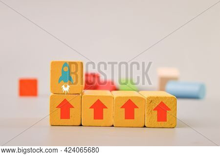 Wooden Blocks With Arrow Up And Rocket Symbols. Start Up, Income And Success Concept