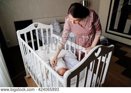 Mom Straighten The Blanket At The Sleeping In The Crib Of The Newborn.