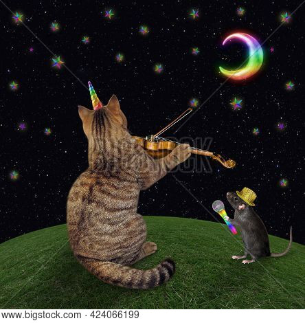 A Beige Cat Unicorn Musician Is Playing The Violin On The Meadow At Moon Night. A Rat Holds A Microp