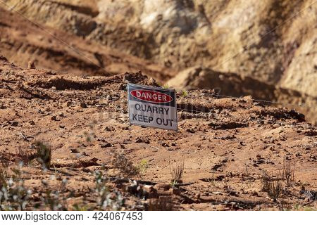 Photograph Of A Keep Out Safety Danger Sign On A Barbed Wire Fence In A Large Quarry