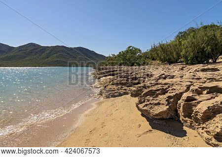 A Rocky Shoreline Of Tropical Coast With Clear Blue Ocean At Low Tide And Sun Glistening On The Wate