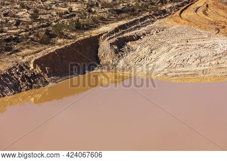 Photograph Of Stagnant Flood Water Lying On The Ground In A Large Quarry