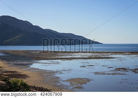 View From A Hilltop Looking Out Over The Coral Sea At Low Tide Under A Clear Blue Sky