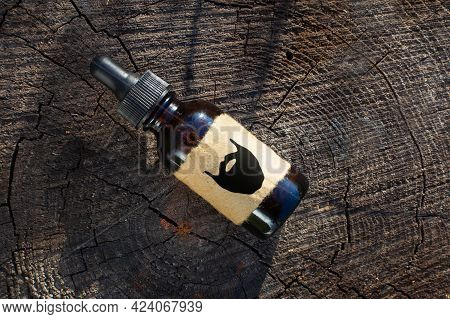 Oil For Care And Growth Of Beard, Barbershop. A Bottle Of Beard Extract On An Old Tree Trunk. Flatle