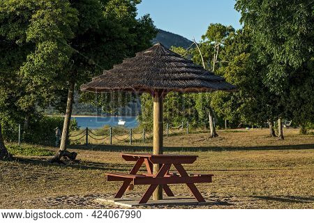 A Straw Thatched Umbrella Shading A Picnic Setting In A Garden At A Beachfront Resort