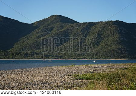 Sail Boats Moored Offshore From A Sandy Beach And A Mountain Background In Late Afternoon Light