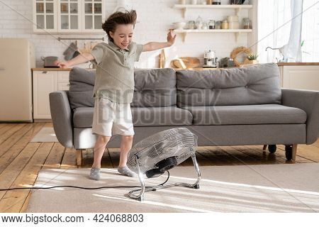 Little Boy Play With Strong Wind Blow From Ventilator Or Industrial Fan At Home In Cozy Living Room.