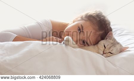 Wide Banner. A Beautiful Little Girl In White Clothes, Lies On A Clean, White Bed With A White Briti
