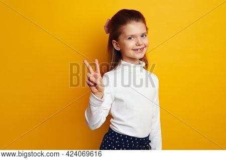 Optimistic Cute Girl Kid Showing Peace Gesture Against Bright Yellow Background