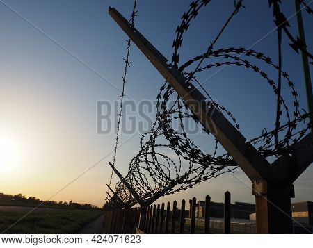 Barbed Wire In Skeins And Stretched Against The Blue Sky. Barbed Wire Against Thieves And Vandals. A