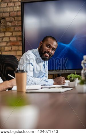 Successful African American Businessman Smiling At Camera Near Lcd Monitor In Conference Room