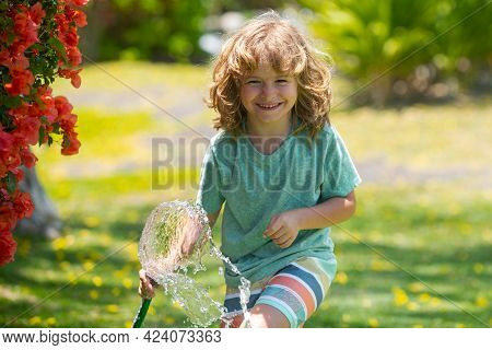 Cute Little Boy Watering Flowers In The Garden At Summer Day. Child Farmer With Garden Hose In Plant