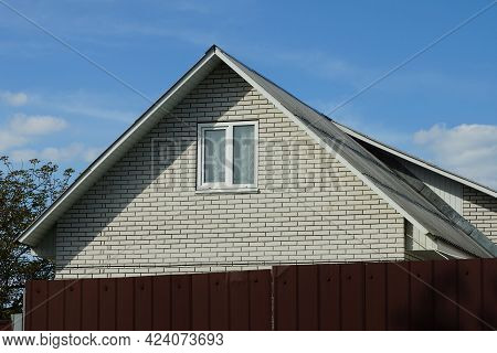 White Brick Attic Of A Private House Behind A Brown Fence Against A Blue Sky