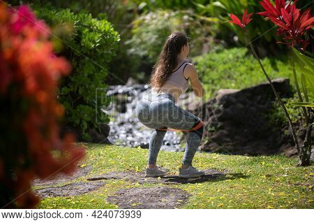 Fit Back And Buttocks. Fitness Woman Doing Squats Exercise For Glute With Resistance Band, Outdoors.