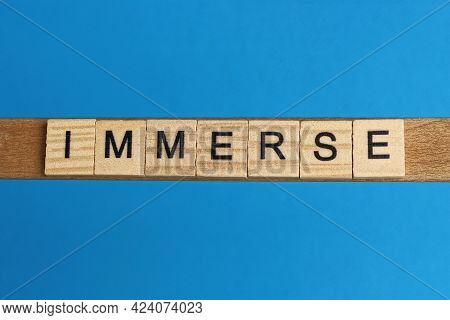Gray Word Immerse In Small Square Wooden Letters With Black Font On A Blue Background
