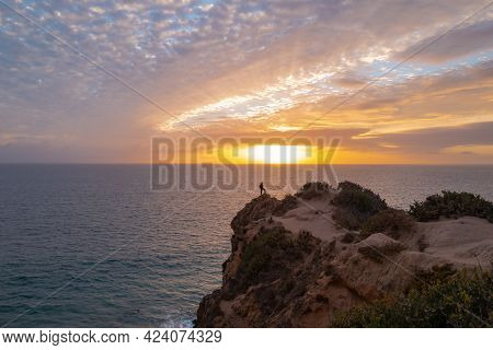 Calm Sea And Rock With Sunset Sky And Sun Through The Clouds Over. Ocean And Sky Background, Seascap