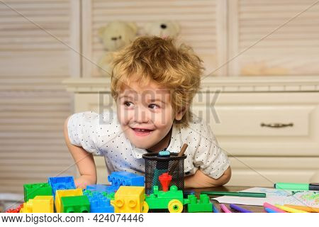 Funny Child Plays In The Constructor In Playroom, Kids Funny Face. Kids Playing With Colorful Blocks