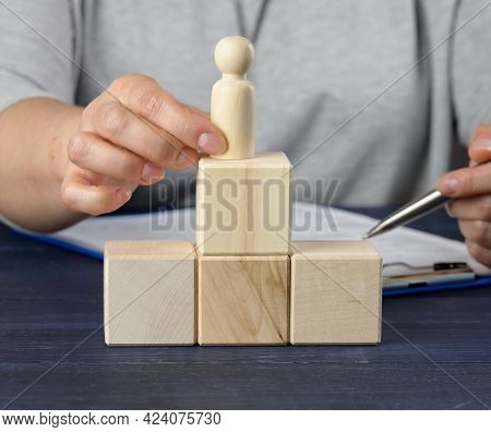 Wooden Cubes In The Shape Of A Ladder And A Figurine Of A Man. Concept Of Career Growth, Goal Achiev