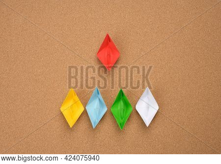 Group Of Paper Boats And One Red On Abrown Background. The Concept Of A Strong Leader, Manipulation