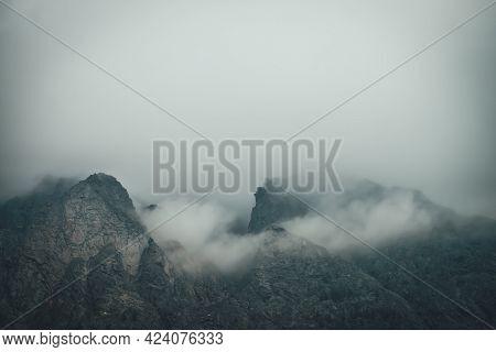 Dark Atmospheric Mountain Landscape With Sharp Rocks In Low Clouds. Dark Rocks In Gray Overcast Weat