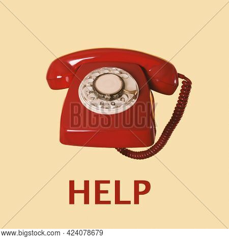 a red landline rotary dial telephone and the text help on a beige background