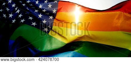 closeup of a rainbow US flag waving on the sky, moved by the wind, with the sun in the background, in a panoramic format to use as web banner or header