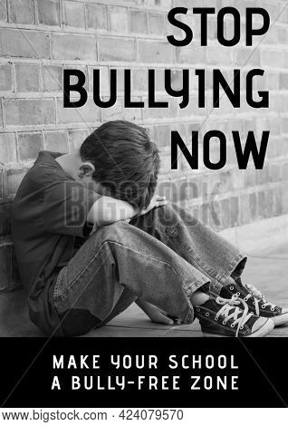 Composition of anti bullying text with crying schoolboy in black and white. childhood, bullying and social issues concept digitally generated image.