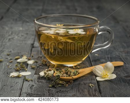 Herbal Tea And Flowers In A Wooden Spoon And A Glass Cup Of Tea. An Invigorating Drink That Is Good