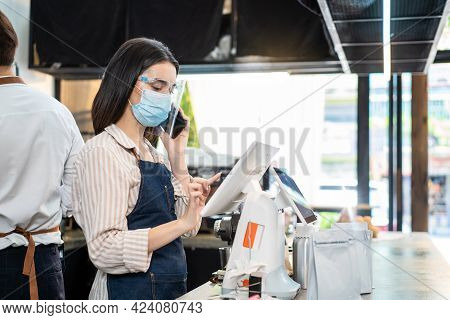 Asian Cafe Business Owner Wear Protective Face Shield And Mask Due To Covid 19, Use Phone Talk To Cu