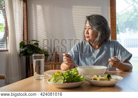 Asian Elderly Retired Grandmother Stay At Home With Painful Face Sitting Alone On Eating Table In Ho
