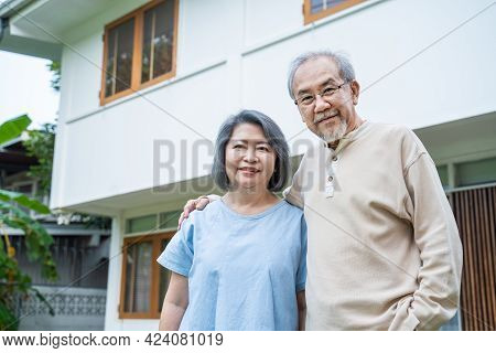 Portrait Of Asian Happy Senior Elderly Couple Stand Outdoor At House Enjoy Retirement Life Together.