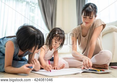 Asian Loving Parent Spend Time With Small Cute Kid Daughter Enjoy Activity At House. Little Siblings