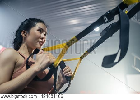 Asian Active Athlete Girl Straight Out Her Arms To Hold Rope Anchored To A Steel Beam In Stadium. Sp