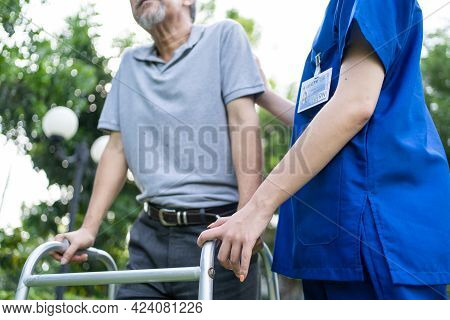 Close Up Of Asian Young Woman Nurse Visit And Take Care Disabled Senior Elderly Man. Caregiver Docto