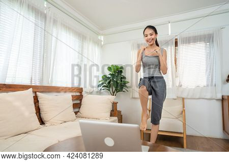 Asian Sporty Young Woman Workout Exercising By Watching Fitness Live Or Video Tutorial Tv Online On