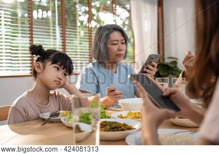 Upset Daughter Sitting At Lunch Table Looking To Addicted Parents And Grandparents Using Smartphones