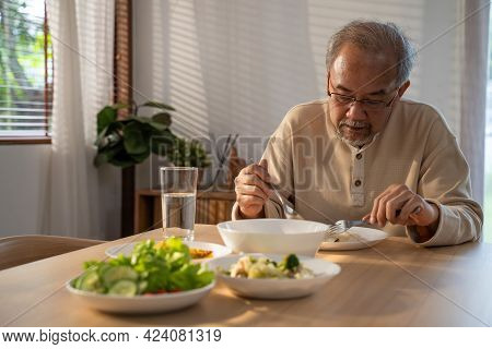 Asian Elderly Retired Grandfather Stay At Home With Painful Face Sitting Alone On Eating Table In Ho